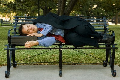 Businessman napping on park bench