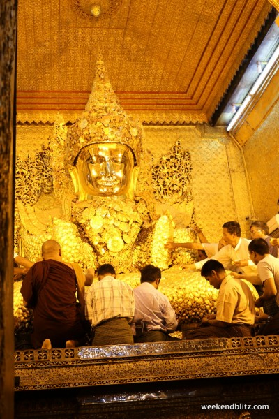 Men applying gold leaf to the Buddah at the M Pagoda